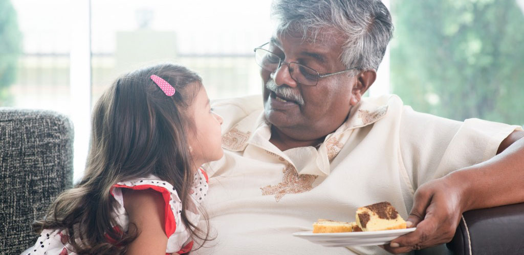 indian-grandfather-eating-cake-with-little-girl